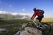 Mountain biker looking at view at Scindarella, Campo Imperatore, Gran Sasso National Park, Abruzzi, Italy, Europe