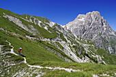 Mountain biker at Corno Grande under blue sky, Campo Imperatore, Gran Sasso National Park, Abruzzi, Italy, Europe
