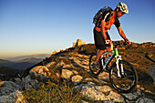 Mountain biker in the mountains, in the background castle Rocca Calascio, Campo Imperatore, Gran Sasso National Park, Abruzzi, Italy, Europe