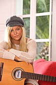 Adult, Adults, At home, Blonde, Blondes, Cap, Caps, Caucasian, Caucasians, Color, Color image, Colour, Contemporary, Daytime, Facing camera, Fair-haired, Female, Guitar, Guitars, Hat, Hats, Headgear, Hobbies, Hobby, Home, human, indoor, indoors, interior,