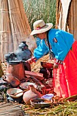 A woman in traditional dress cooking a meal on the floating Islands in Lake Titicaca, Peru, South America