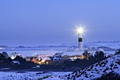 Lighthouse Kampen on snow covered fields in operation with the light beam visible, seen from abvoe with the traditional houses of the village of Kampen and a bright blue sky of the early evening, Sylt, Northfrisian Islands, Schleswig-Holstein, Northern Ge
