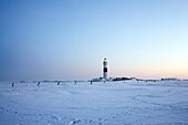 Lighthouse Kampen on snow covered fields with a bright blue sky during sun set, in operation with the light beam visible, Sylt, Northfrisian Islands, Schleswig-Holstein, Northern Germany, Europe