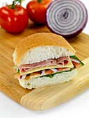 A ham and salad roll isolated against a white background