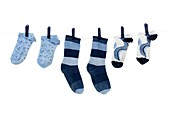 Socks hanging from a clothes line isolated against a white background