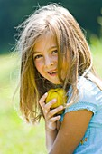 Six year old girl is holding a pear