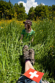 Girl and adult resting in meadow at mount Niesen, Bernese Oberland, Canton of Bern, Switzerland