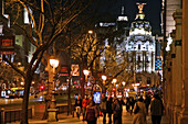 Sidewalks At Night On The Calla Alcala With The Metropolis Building Surmounted By A Bronze Statue Of The Phoenix, Madrid, Spain