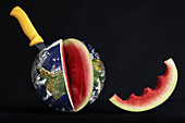 Knife Stuck Into A Watermelon In The Form Of The Earth With A Slice Bitten Out Of It, Illustration Of The Consumption Of The Planet's Natural Resources, Photo Exhibition 'Fragile Earth' Presented By The Association 'L'Effet Colibri' France