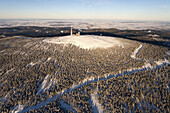 Aerial view above the snow covered Brocken mountain in Harz National Park with transmitter site, Saxony-Anhalt, Germany