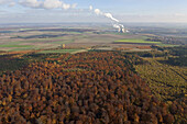 Aerial view of mixed forest in autumn colours, Elm-Lappwald nature park, UNESCO Geo park, Buschhaus coal-fired power plant in background, Lower Saxony, Germany