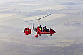 Aerial view of a two-seater autogyro, gyrocopter with cameraman, Lower Saxony, Germany
