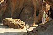Woman walking through rock with bizarre eolian erosion, Namib desert, Namib, Namibia