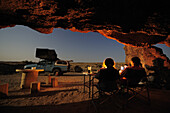 Group of people sitting under overhang, car with roof tent in background, stone desert, Namib Naukluft National Park, Namib desert, Namib, Namibia