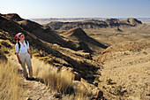 Woman walking on track in Naukluft mountains, Olive trail, Namib Naucluft National Park, Namibia