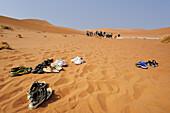 Several pairs of shoe in red sand, group of people in background, Sossusvlei, Namib Naukluft National Park, Namib desert, Namib, Namibia