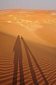 Two people holding hands throwing shadow on red sand dunes, Namib Rand Nature Reserve, Namib desert, Namib, Namibia