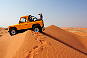Woman sitting in open jeep on red sand dune, Namib Rand Nature Reserve, Namib desert, Namibia