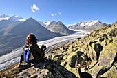 Woman enjoying view from mount Bettmerhorn over Aletsch Glacier, Canton of Valais, Switzerland