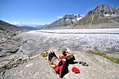 Couple sunbathing near Aletsch Glacier, Canton of Valais, Switzerland
