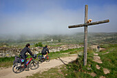 Pilgrims on bicycles at a wayside cross, Province of Leon, Old Castile, Castile-Leon, Castilla y Leon, Northern Spain, Spain, Europe