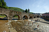 People in front of bridge at the river Rio Meruelo, Molinaseca, Province of Leon, Old Castile, Castile-Leon, Castilla y Leon, Northern Spain, Spain, Europe