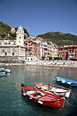The village of Vernazza is set against rugged mountain terrain that overlooks the Ligurian Sea in Italy