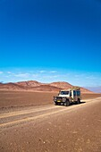 A landrover driving through the isolated Skeleton Coast Park in Namibia, Africa