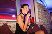 Young woman having a drink in Eastwest Beach Club, Dubrovnik, Dubrovnik-Neretva county, Dalmatia, Croatia