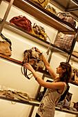 Woman choosing a handbag in Adolfo Dominguez designer shop, Province Valencia, Valencia, Spain