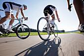 Three racing cyclists on road near Munsing, Upper Bavaria, Germany