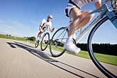 Two racing cyclists on road near Munsing, Upper Bavaria, Germany