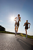 Two runners on road near Munsing, Upper Bavaria, Germany