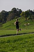 Male runner on path near Munsing, Upper Bavaria, Germany