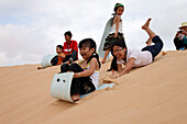 Children sliding on White Dunes, Mui Ne, Binh Thuan, Vietnam