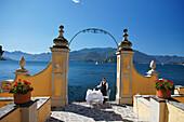 Außen, Mitarbeiterin deckt Tisch, Hotel Royal Victoria, Varenna, Comer See, Lombardei, Italien