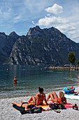 Women sunbathing on the beach, Torbole, Lake Garda, Trento, Italy