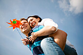 Mid adult man giving woman with pinwheel a piggyback ride