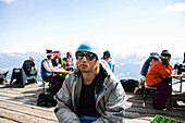 Man sitting on terrace of Cafe No Name, Flims Laax Falera ski area, Laax, Grisons, Switzerland