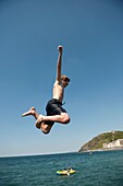 A man jumping into the sea, Aberystwyth seaside resort, wales UK, summer afternoon