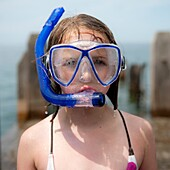 Close up of a 10 year old girl wearing a diving mask and snorkel after being in the water, UK