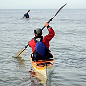 rear view of two people paddling sea kayaks, UK