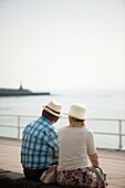 Rear view of an adult senior couple, man woman, sitting outside wearing hats, Summer afternoon, Aberystwyth Ceredigion wales UK