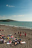 A group of students relaxing after their exams and playing on Aberystwyth beach, Cardigan Bay, West Wales, UK