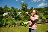 A woman juggling with three potatoes at The Centre for Alternative Technology, Machynlleth, Powys Wales UK