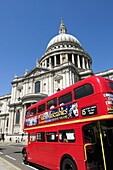 An old Routemaster double decker bus with Les Miserables advert passing St Pauls Cathedral, London, England, UK