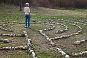 Prairieville, Michigan - A woman stands at the center of a labyrinth at Circle Pines camp The labyrinth is an aid to meditation the spiritualism © Jim West