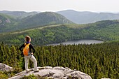 young woman admiring landscape with Pioui lake, Pioui path, Grands-Jardins National Park, Province of Quebec, Canada, North America