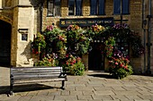 A floral display outside the National Trust gift shop by Penniless Porch in the Market Place, Wells, Somerset, England, United Kingdom