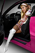 Young fashionable attractive woman in a short fancy dress and white boots sitting in a car